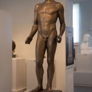 """«Μνήμη Σπύρου Λούη» (1989). Χαλκός 1,30μ. Η αρχική ονομασία του γλυπτού ήταν «Έφηβος». Το άγαλμα δεν αναπαριστά τον ολυμπιονίκη Σπύρο Λούη, αλλά μέσω του γυμνού έφηβου τιμά τον αθλητή. Οι έξοχες σωματικές αναλογίες του δημιουργούν έναν σύγχρονο Κούρο, που εμπνέεται από τα αρχαία πρότυπα. Βρίσκεται κοντά στο Παναθηναϊκό Στάδιο Αθηνών και στο Μουσείο Γλυπτικής """"Νίκος Περαντινός"""" στη Μάρπησσα."""